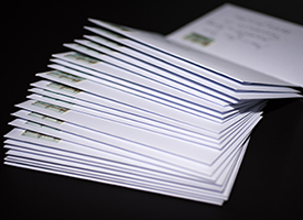 Stack of franked letters in white envelopes on black background